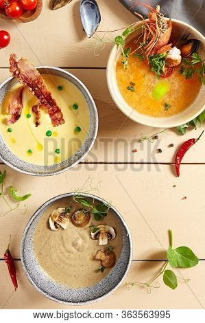 Soups in ceramic bowls top view. Potato cream with bacon and onion baguette, tom yum, forester soup with cheese rusks. First courses, served broths, european and asian cuisine meals