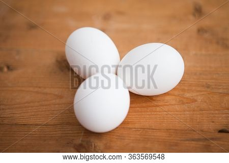 Three White Eggs On The Wooden Background
