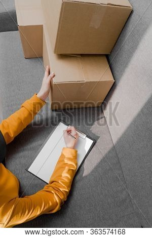 Girl Manager Makes A List Of Things That Lie In Cardboard Boxes. Inventory Of The Warehouse.