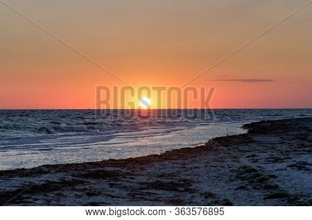 Seacoast, Sea With Waves And Big Bright Sun Over The Horizon. Calm Dawn Over The Sea. Dawn On The Co