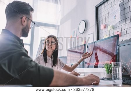 Selective Focus Of Data Analyst Pointing With Hand On Computer Monitor To Colleague In Office