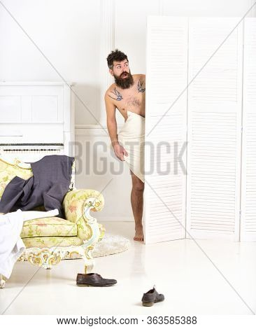 Man, Lover In White Interior Caught Naked. Man With Beard And Mustache Hiding Behind Folding Screen.