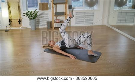 View From The Side As A Girl Is Engaged In Fitness At Home On The Floor. Girl Trainer Doing Exercise