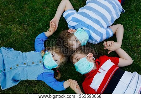 Three Kids, Little Toddler Girl And Two Kid Boys In Medical Mask As Protection Against Pandemic Coro