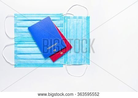 Two Foreign Passports Of Blue And Red Colors Are On Medical Masks On A Light Background. World Quara