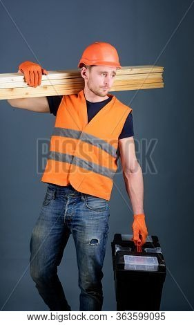 Woodcraft Concept. Man, Handyman In Helmet, Hard Hat Holds Toolbox And Wooden Beams, Grey Background