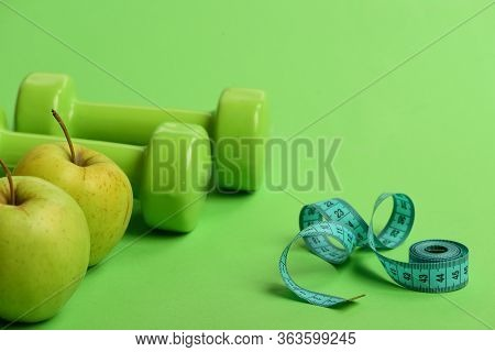 Diet And Sport Regime Concept. Tape Measure Near Barbells