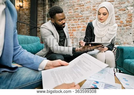 Business Concept Of Signing The Joint Contract. Beautiful Muslim Business Lady In White Hijab Sittin
