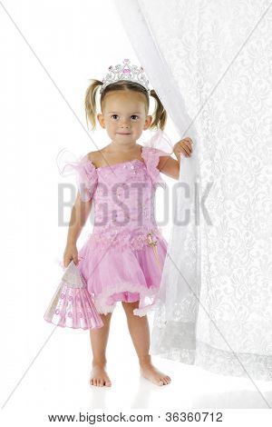 A beautiful preschool princess happily holding a folding fan in one hand while pulling back a lacy curtain in the other.  On a white background.