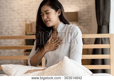 Portrait Of 20s Young Asian Woman Having Difficulty Breathing In Bedroom At Night. Shortness Of Brea