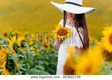 Beautiful Sweet Young Woman In A White Dress And Hat In A Field Of Sunflowers. Girl Is Holding Sunfl