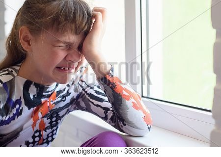 Teen Girl Crying A Lot While Sitting By The Window In The Room, Close-up