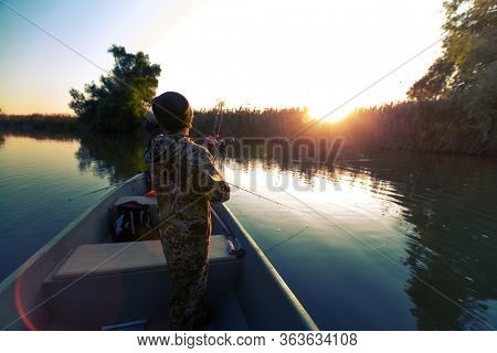 Anglers fishing from the boat on the calm river in Astrakhan Region in Russia. Astrakhan is a famous fishing destination