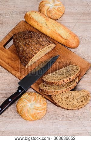 Different Breeds On Wooden Background. Knife On A Wooden Board With Bread And Different Buns On The