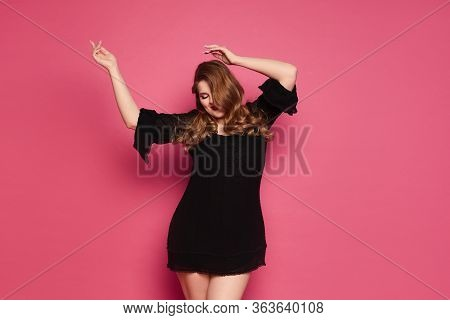 Young Xxxl Woman, Happy Plus Size Model Girl In Short Black Dress Dancing At The Pink Background, Is