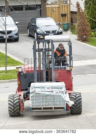 Toronto, Canada - April 28, 2020: Workman Driving A Red Forklift To Move A Pile Of Concrete Patio St