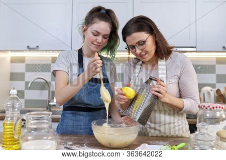 Mother And Teenager Daughter Cook Together At Home In Kitchen. Girl Helps Her Mom Stir Dough, Woman