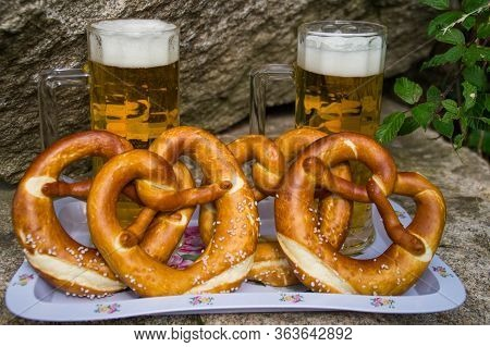 Beer With A Pretzel Stands On A Countertop By The Stones. 4 Pretzels, Two Glasses Of Beer. Festiviti