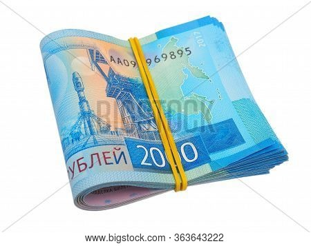 A Rolled Up Bundle Of Russian Rubles In 2000 Rubles Lies On An Isolated White Background. Banknotes