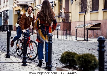 Mirthful Cycler Looking Happy To Meet His Friend In The Street