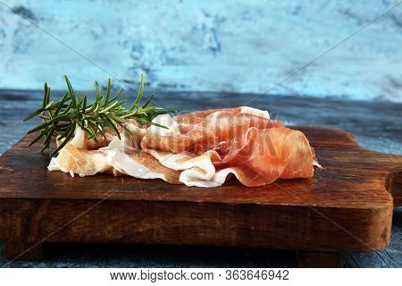 Italian Prosciutto Crudo Or Jamon With Rosemary. Raw Ham Appetizer
