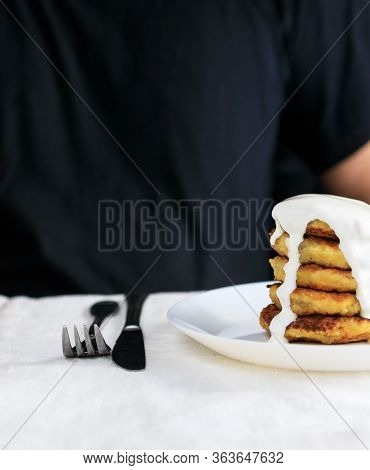 A Clipped Man In Black Clothes Sits At A Table With A Linen Light Tablecloth With Curd Cheese Pancak