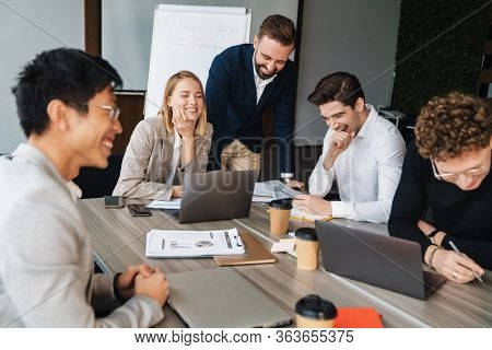 Group of smart multiethnic motivated businesspeople working together on a new project while sitting at the table in the office