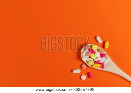 Mixed Medicine Pills, Tablets On Wooden Spoon On Orange Background. Many Different Pills And Tablets