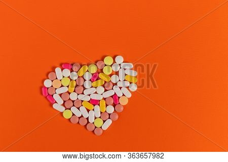 Many Different Pills And Tablets Folded In Shape Of Heart On Orange Background. Many Pills And Table