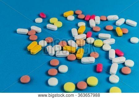 Different Medicine Pills, Tablets On Blue Background. Many Medicine Pills And Tablets. Health Care.