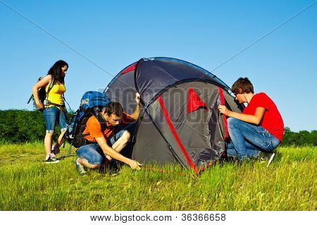 Teens setting a camping tent