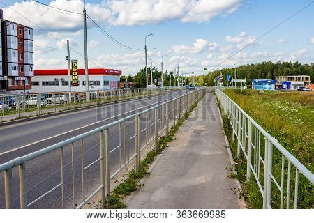 Kabitsino, Russia - August 2019: A Metal Fence Between The Road And The Sidewalk, A Fence On Both Si