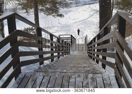 View Of The Steep Descent Down The Wooden Stairs With Railings Down To The River In The Winter Park,
