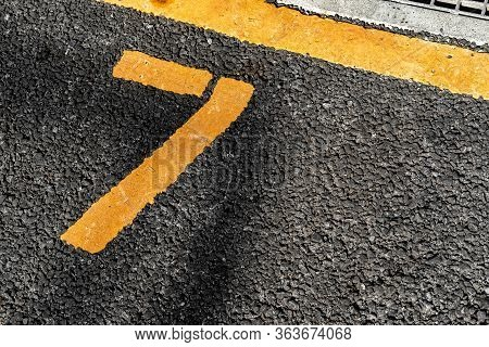 Asphalt Parking Lot With Yellow Lot Line And Yellow Lot Number 7, Seven, Seventh.