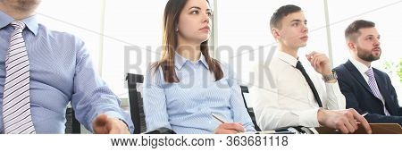 Portrait Of Gorgeous Woman And Men Sitting In Modern Conference Room And Discussing Important Busine