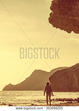 Tourist Woman Walking With Camera, Taking Travel Picture On Monsul Beach. Cabo De Gata Nijar Natural