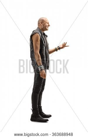 Full length profile shot of a bald punk man in a leather clothing gesturing with hand isolated on white background