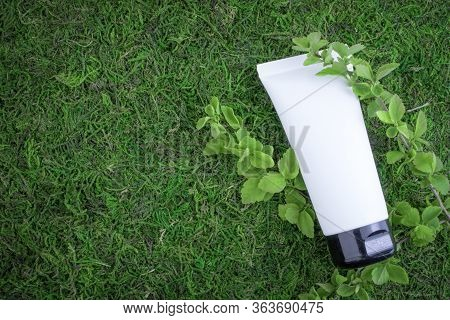 White Unlabelled Cosmetic Bottle, On A Green Natural Background, Grass, Moss With Branches Of Greene