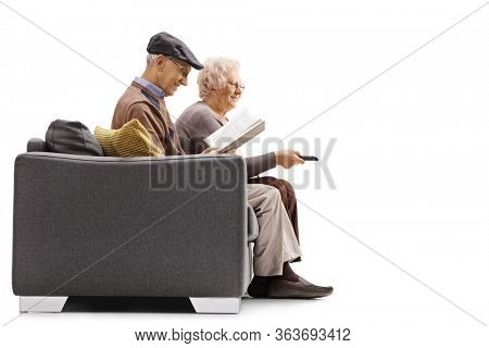Profile shot of an elderly man reading a book and an elderly woman watching tv and sitting on a sofa isolated on white background
