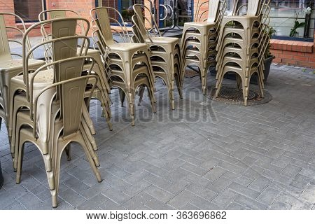 Stacked Chairs In A Street Cafe That Is Not Allowed To Open Because Of The Coronavirus Crisis, Econo