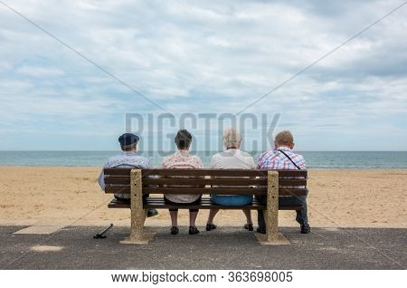 Rear view of four anonymous senior people, old couples, elderly men and women sitting on a bench at a beach