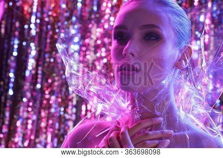 High Fashion Model Girl In Colorful Bright Neon Lights Posing In Studio Through Transparent Film. Po