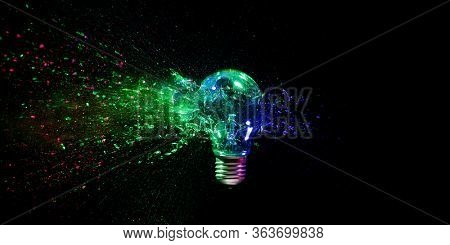 high speed image of a real explosion of a traditional tungsten light bulb. black background, colored lights. concept of fragility, crisis and obsolete energy.