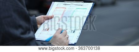 Close-up Of Male Hands Holding Clipboard With Documentations And Writing Down Something. Accident St