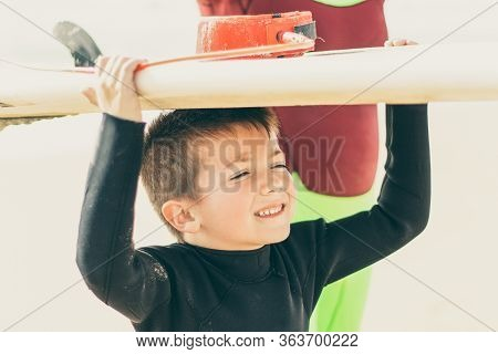 Cute Little Boy Holding Surfboard. Adorable Smiling Child In Wetsuit Holding Surfboard And Looking A