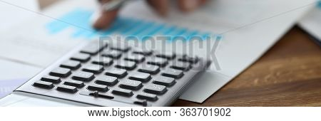 Close-up Of Calculator On Wooden Table. Accountant Making Annual Financial Statement. Worker Prepari