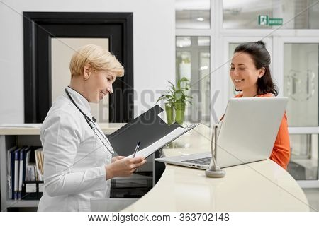 Side View Of Cheerful Female Doctor With Stethoscope On Neck Checking Documents In Folder Behind Rec