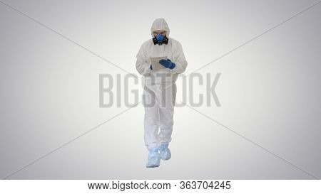 Epidemiologist In Hazmat Suit And Respirator Mask Using Digital Tablet While Walking On Gradient Bac
