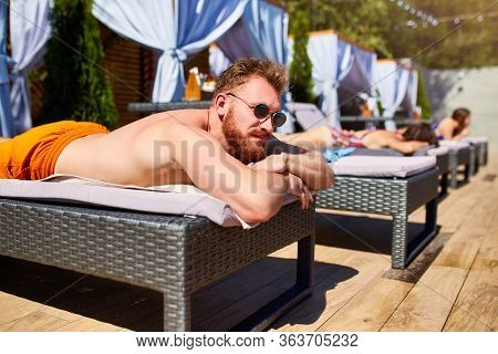 Man In Sunglasses Chilling On Lounger With Friends At Poolside. Handsome Guy Relax At Luxury Resort