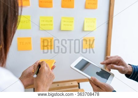 Business People Arranging Sticky Notes Commenting And Brainstorming On Work Priorities Colleague In